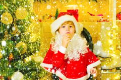 Merry Christmas. Santa - funny child picking cookie. Santa Claus takes a cookie on Christmas Eve as a thank you gift for