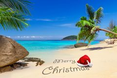 Merry Christmas wishes from the tropical beach. Merry Christmas with santa hat from the tropical beach Royalty Free Stock Images