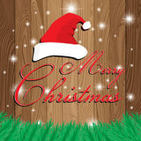 Merry Christmas and Santa`s cap on wooden background. Christmas tree on Lath boards background. Royalty Free Stock Photography