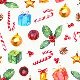 Merry Christmas seamless pattern. Watercolor Illustration with holly berry, candy cane, balls, gifts and gold bells isolated on white background Stock Photography