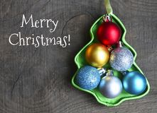Merry Christmas.Christmas set of colorful shiny balls inside of christmas tree shaped box on old wooden background.Christmas decor Royalty Free Stock Photos