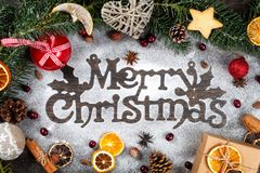 Merry Christmas sigh made out of sugar powder surrounded by Christmas holidays ornament, flat lay.  royalty free stock photos