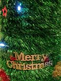 Merry Christmas sign decoration on the green tinsel with light stock photography
