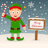 Merry Christmas Sign with a Green Elf Stock Images