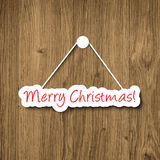 Merry Christmas sign hanging on a wood plank Royalty Free Stock Image