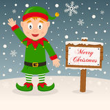 Merry Christmas Sign - Happy Green Elf. A merry Christmas greeting card with a happy green elf smiling in a snowy scene with a merry Christmas wooden sign. Eps Royalty Free Stock Photo