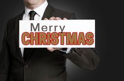 Merry Christmas sign held by businessman concept Stock Images
