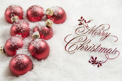 Merry Christmas Sign and Ornaments in Snow Royalty Free Stock Photos