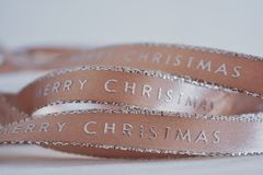 Pink Christmas ribbon on a white background royalty free stock image