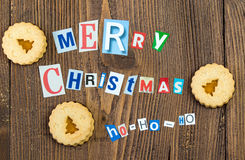 Merry Christmas slogan made from newspaper letters with cookies. Merry Christmas slogan made from newspaper letters with christmas cookies on a natural wooden Royalty Free Stock Images