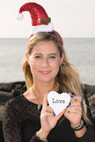 Merry Christmas. A smiling young woman with a Christmas hat and the word love Stock Images