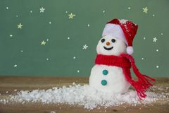 Merry christmas Snowman. Merry christmas and Happy new year. White Snowman hat and scarf red on snow wooden floorand and green board background space leave blank Royalty Free Stock Image