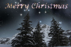 Merry Christmas in starry sky. Merry Christmas in a winter landscape of snowy mountain in a starry sky Stock Photography