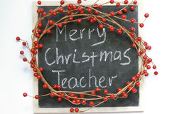 Merry Christmas Teacher. Merry Christmas Teacher message surrounded by red berry Christmas wreath on an old scratched black board written in white chalk stock image