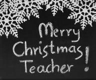Merry Christmas Teacher, blackboard. Merry Christmas Teacher message handwritten in white chalk on a traditional school blackboard. The blackboard is decorated stock photo