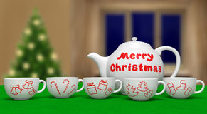 Merry Christmas. Teapot and cups with xmas symbols on blurred background. White ceramic teapot with text and cups with xmas symbols on green table on blurred Royalty Free Stock Image