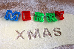 Merry Christmas text, baking Christmas cookies Royalty Free Stock Photo