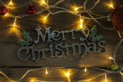 Merry Christmas text framed by Christmas lights. Top view of Merry Christmas text framed by Christmas lights on the wooden table stock images