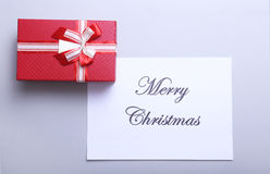 Merry Christmas text with gift boxes on white wood background, top view Royalty Free Stock Photos
