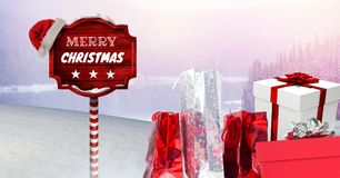 Merry Christmas text and gifts with Wooden signpost in Christmas Winter landscape and Santa hat. Digital composite of Merry Christmas text and gifts with Wooden Royalty Free Stock Photos