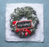 Merry Christmas text lettering. Wreath with green fir branches and red framed sign and Santa hat in snow on blue background, top v. Iew . Holiday layout concept stock photography