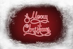 Merry Christmas text on red background and hoarfrost snow frost on xmas window Stock Images