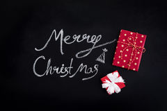 Merry Christmas text with red gift boxes on blackboard Stock Photo