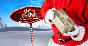 Merry Christmas text and Santa holding gifts with Wooden signpost in Christmas Winter landscape. Digital composite of Merry Christmas text and Santa holding Royalty Free Stock Photos
