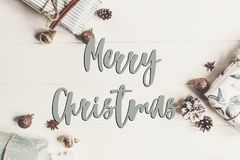 Merry christmas text, seasonal greetings card sign. flat lay. pr. Esents with ornaments and pine cones anise on white wooden background top view Royalty Free Stock Images