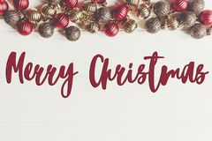 Merry christmas text, seasonal greetings card sign. flat lay. re. D and gold christmas ornaments  frame or border on white wooden background top view Royalty Free Stock Photography
