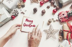 Merry christmas text, seasonal greetings card sign. hands holdin Stock Photography