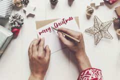 Merry christmas text, seasonal greetings card sign. hands holdin Royalty Free Stock Image