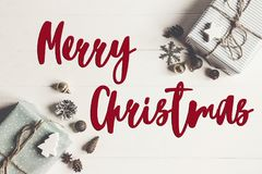 Merry christmas text, seasonal greetings card sign. modern chris. Tmas wrapped presents with ornaments and cones on white wooden background top view Stock Photos
