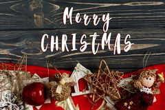 Merry christmas text sign on christmas frame of golden stylish t. Oys. ornament border on black rustic wooden background. space for text. holiday greeting card royalty free stock photos