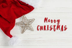 Merry christmas text sign on  golden star and santa hat on white. Rustic wooden background. space for text. holiday greeting card concept. unusual creative top Royalty Free Stock Image