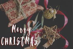 Merry christmas text sign on  gorgeous present in design paper w Royalty Free Stock Images