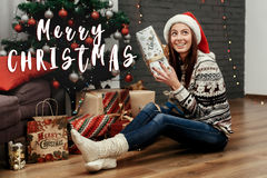 Merry christmas text sign greeting with beautiful happy woman ho Royalty Free Stock Photo