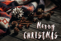 Merry christmas text sign greeting on stylish winter or autumn w. Allpaper. anise cinnamon and pine cones on wooden rustic background. space for text. cozy mood Stock Images