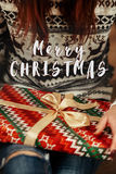 Merry christmas text sign greeting on woman in sweaters with dee Royalty Free Stock Images