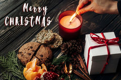 Merry christmas text sign on hand lighting up candle and present Royalty Free Stock Photography
