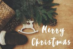 Free Merry Christmas Text Sign On Reindeer Toy, Gloves, Basket With Fir Branches And Cones On Rustic Wooden Background. Flat Lay. Zero Stock Photography - 164238802