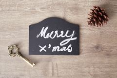 Merry christmas text sign with pine cone and key ornament Stock Image