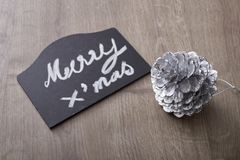 Merry christmas text sign with pine cone ornament Royalty Free Stock Image