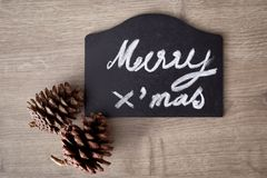 Merry christmas text sign with pine cone ornament Royalty Free Stock Photos