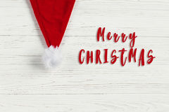 Merry christmas text sign on red santa hat on white rustic woode. N background. space for text. holiday greeting card concept. unusual creative view Stock Photography
