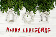 Merry christmas text sign on simple toys on green tree branches. On stylish white rustic wooden background. space for. holiday greeting card concept. unusual Stock Photo