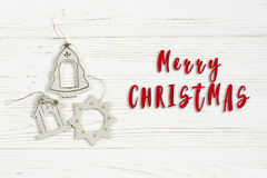 Merry christmas text sign on simple vintage toys on stylish whit. E rustic wooden background. space for text. holiday greeting card concept. unusual creative top Royalty Free Stock Image