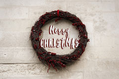 Merry christmas text sign in stylish minimal simple christmas wr. Eath on old wall, celebration decoration for holidays in the city. seasonal greetings Royalty Free Stock Photo