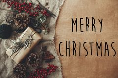 Merry Christmas text sign on stylish rustic christmas gift box with fir branches, red berries, pine cones on rustic wood. stock photos