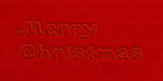 Merry Christmas text velvet background. Merry Christmas holiday background. Embossed extruded text inscription embroider in gold over the silk velvet (plush Stock Images